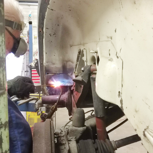 Schweißarbeiten an einem VW Käfer aus den 70ern